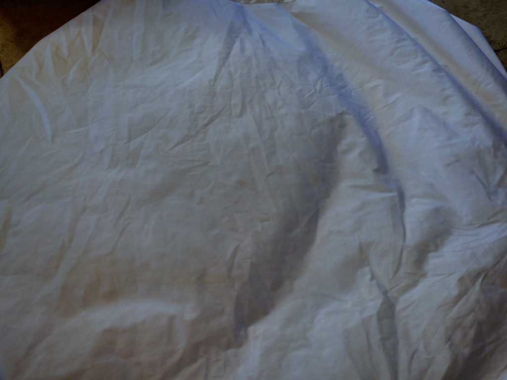Purple mattress protector after being drenched in wine and then washed