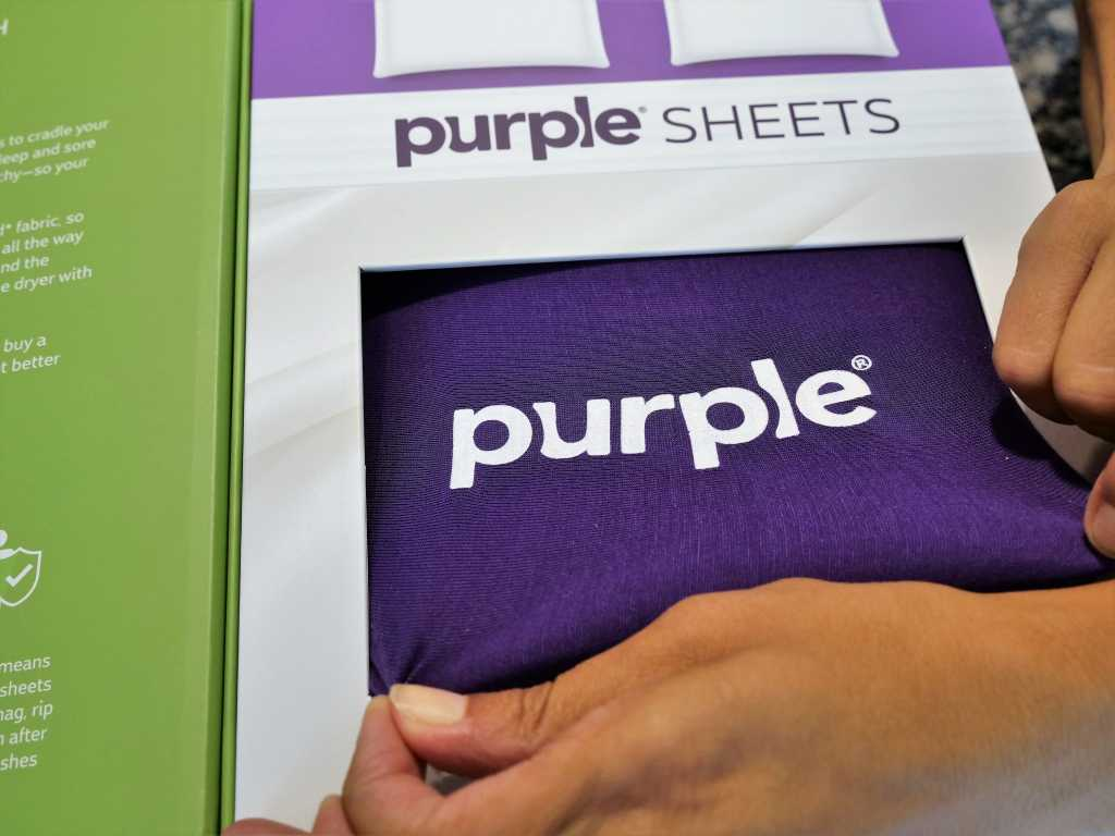 stretching the purple sheets through the box's window